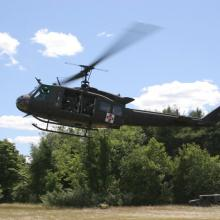 An UH-1 Huey equipped as an Air Ambulance (Med evac) helicopter takes off.